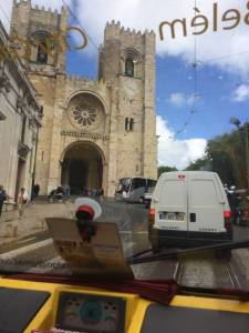tuktuk passing by lisbon cathedral
