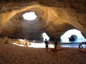 The Benagil cave has two openings to the sea, and a hole in the top, and you can walk over it by land.